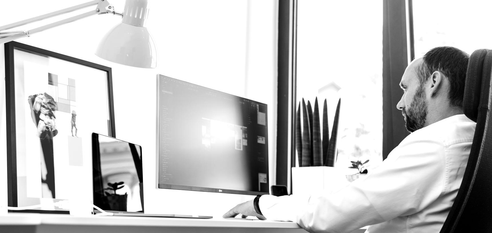 Pedja Zdravkovic at his workstation looking at the computer